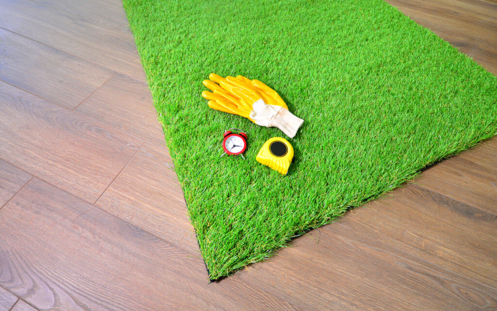 Artificial grass on the floor with alarm clock, measure tape, protective glooves. Quick lawn mowing idea.