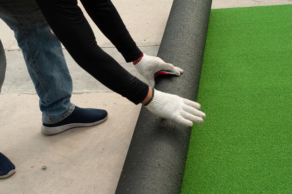 man rolling artificial grass